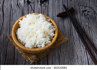 Cooked rice in wooden bowl on a wooden table, Thai food rustic style