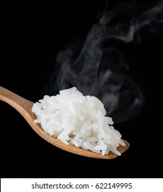 Cooked rice in a wooden spoon with smoke over dark background