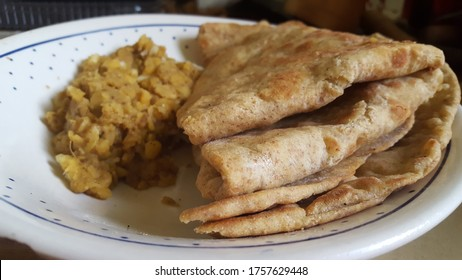 Cooked Sada, Whole Wheat, Tortilia Wrap or Roti with cooked curried potato on a plate.