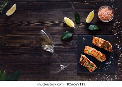 Cooked salmon with white wine on wooden background. Lemon slices, bay leaves and himalaya salt. Top view. Copy space. Right oriented