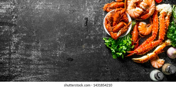 Cooked shrimp, crayfish and crab with parsley. On dark rustic background