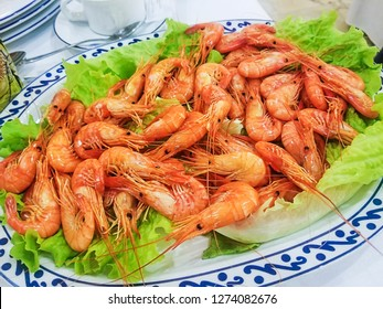Cooked shrimp Palaemon serratus served on tray over lettuce leaves