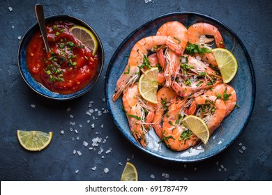 Cooked shrimps on plate with lemon, salt, sauce. Seafood appetizer. Top view. Big red prawns for lunch on rustic stone background. Healthy clean eating/diet. Shrimps close-up. Prepared large prawns