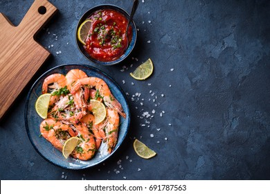 Cooked shrimps on plate with lemon, salt, sauce. Seafood appetizer. Space for text. Top view. Big red prawns for lunch/dinner on rustic stone background. Healthy clean eating/diet. Shrimps for snack
