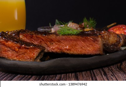 cooked steak with fried tomatoes, onions , dill and rosemary.selective focus, close-up