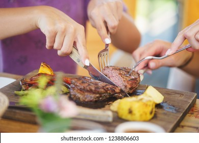 Cooked steak piece of meat on a wooden board with vegetables and potatoes on the table in the restaurant. Lunch in a restaurant in a large company, friends share a delicious steak.