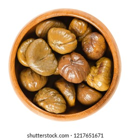 Cooked sweet chestnuts in wooden bowl. Edible seeds or nuts of Castanea sativa, also called marron and Spanish or Portuguese chestnut. Isolated macro food photo closeup from above on white background.