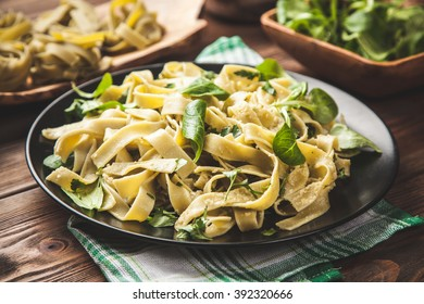 Cooked tagliatelle pasta with greens and grated parmesan cheese