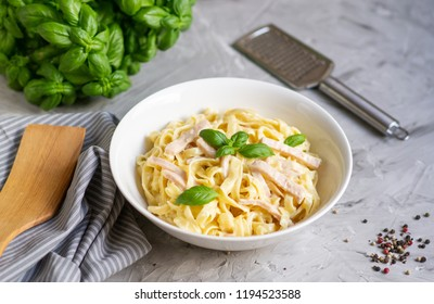 Cooked tagliatelle pasta on a plate with Carbonara sauce, bacon, basil and Parmesan cheese, Italy food, healthy concept,