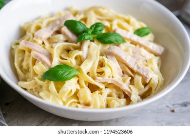 Cooked tagliatelle pasta on a plate with Carbonara sauce, bacon, basil and Parmesan cheese, Italy food, healthy concept
