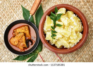 Cooked tapioca or Cassava root , Mandioca or Aipim with  spicy Fish curry, Kerala, India. Prepared with grated coconut South Indian food, Kappa Puzhukku, served with chutney. root vegetable Brazil.