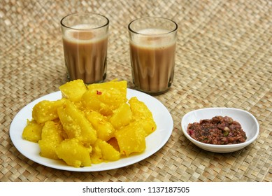 Cooked tapioca or Cassava root , Mandioca or Aipim, chutney and tea, Kerala, India. Prepared with grated coconut South Indian food, Kappa Puzhukku, served with Fish curry. root vegetable Brazil.