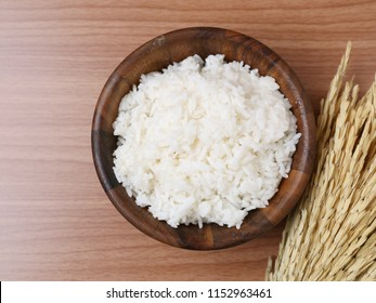 Cooked Thai jasmine rice with copy space on wooden background.