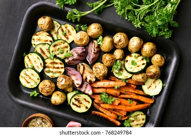 Cooked vegetables on baking tray over dark background. Roasted carrot, zucchini, potato, onion. Top view, flat lay.