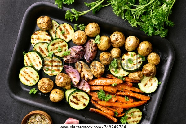 Cooked vegetables on baking tray over dark background. Roasted carrot, zucchini, potato, onion. Top view, flat lay