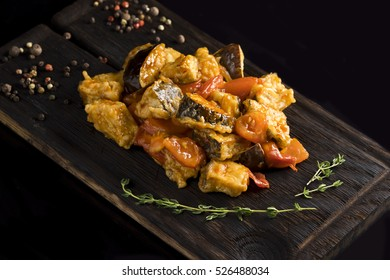 cooked vegetables, pepper, rosemary on a wooden board