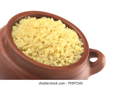 Cooked white quinoa in rustic bowl which can be eaten as a side dish like rice and is rich in proteins isolated on white (Selective Focus, Focus on the front of the quinoa)