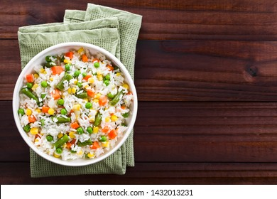 Cooked white rice mixed with colorful vegetables (onion, carrot, green peas, corn, green beans) in white bowl, photographed overhead with copy space on the right side