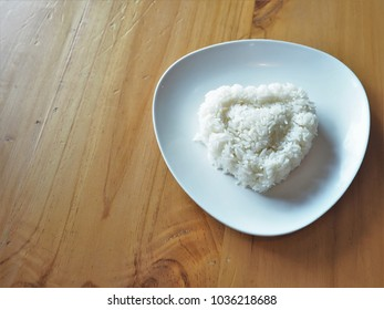 Cooked white rice in a plate on wooden table.