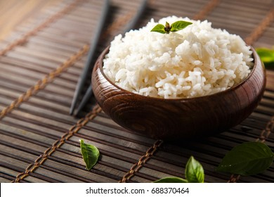 Cooked white rice (Thai Jasmine rice), rice in dark wooden bowl with chopsticks on the wood black bamboo background.