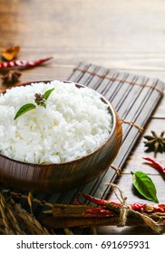 Cooked white rice (Thai Jasmine rice), with herbs, spices, pepper, rice in dark wooden bowl with chopsticks on the wood black bamboo background.