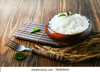 Cooked white rice (Thai Jasmine rice), with herbs, spices, pepper, rice in dark wooden bowl with fork on the wood black bamboo background.