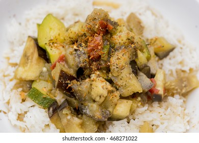 Cooked white rice, tomato, eggplant and zucchini dinner close up. Various herbs sprinkled on top.