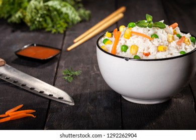 Cooked white rice with vegetables in a bowl with sauces and chopsticks on a wood black background.
