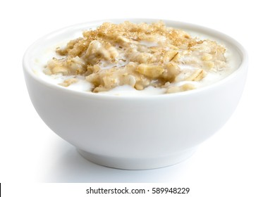 Cooked whole porridge oats with milk and brown sugar in white ceramic bowl isolated on white.