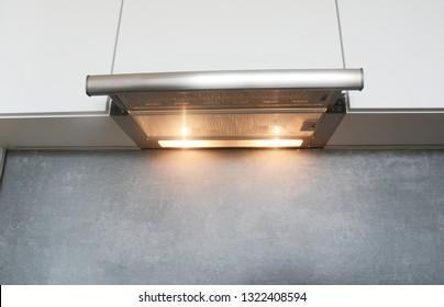 Cooker Hood. Modern air exhauster kitchen fan or range hood. Stainless steel chimney hood. Island hood.