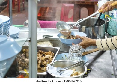 Cooker making thai noodle of jumbo beef ball with meaty sell on cart at night. Thai street food. Thai local food.
