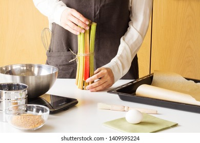 Cooker in wooden kitchen in brown apron with rhubarb in his hands is preparating a rhubarb cake with some kitchen supplies