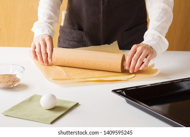 Cooker in wooden kitchen in brown apron stands behind white table. There is dough before him and some kitchen supplies. He is rolling out a dough.
