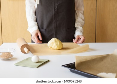 Cooker in wooden kitchen in brown apron stands behind white table. There is dough before him and some kitchen supplies