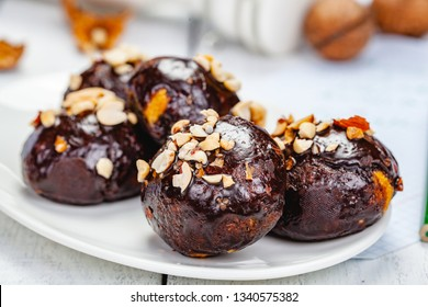 Cookie balls with chocolate glaze and walnuts on white plate. Close up