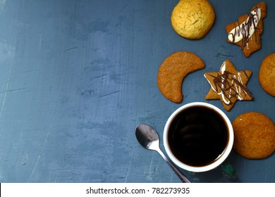 Cookie and cup of coffee on blue wooden table. Food background.