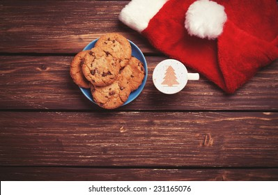 Cookie and cup of coffee with santa's hat on wooden table. Photo in retro color image style.