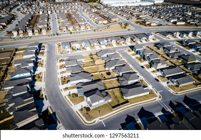 Cookie cutter homes and houses in massive urban suburb north Austin , Texas - Aerial drone view above suburbia housing development