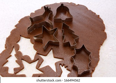 Cookie cutters and cut out shapes on gingerbread dough - star, reindeer, Christmas tree, holly leaf and bell