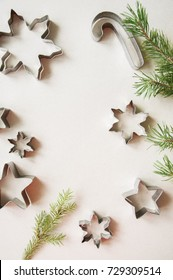 Cookie cutters and fir tree brunches on a wooden background. Flat lay.