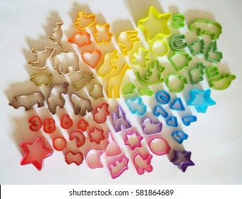 Cookie cutters are plastic. The colors of the rainbow for kids. Homemade pastries. White background.