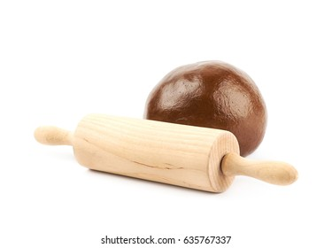 Cookie dough ball next to a rolling pin, composition isolated over the white background