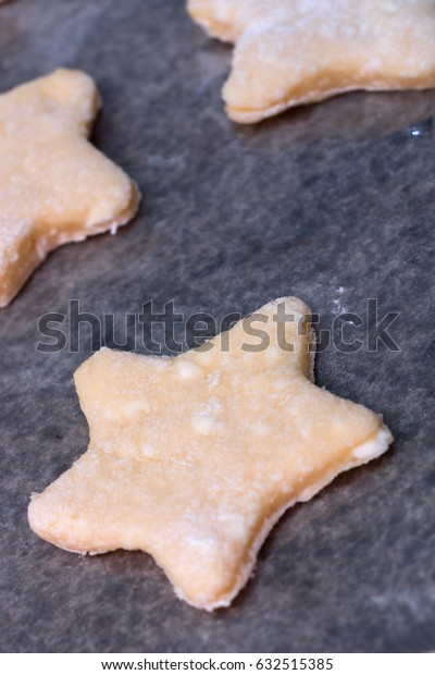 Cookie dough in different shapes lies on the baking sheet.