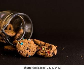 Cookie jar on black background with biscuits spilling out.