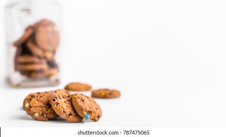 Cookie jar on white background with smartie choc chip biscuits