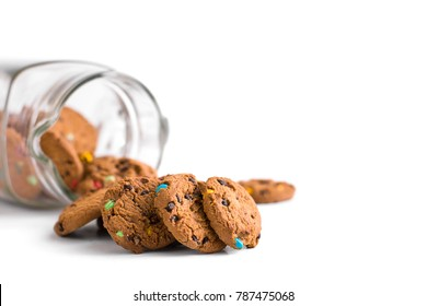 Cookie jar on white background with biscuits spilling out.