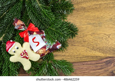 a cookie man and a Christmas bag lying on fir branches