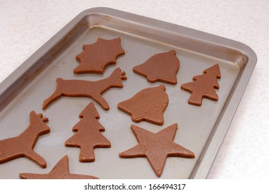 Cookie sheet with uncooked gingerbread biscuits in festive shapes