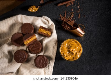 cookies alfajores with cream dulce de leche on black stone, macaroons covered with chocolate top view