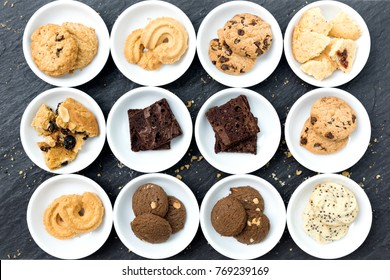 Cookies and brownie in white ceramic container flat lay on table top, Top view different cookies in white bowl